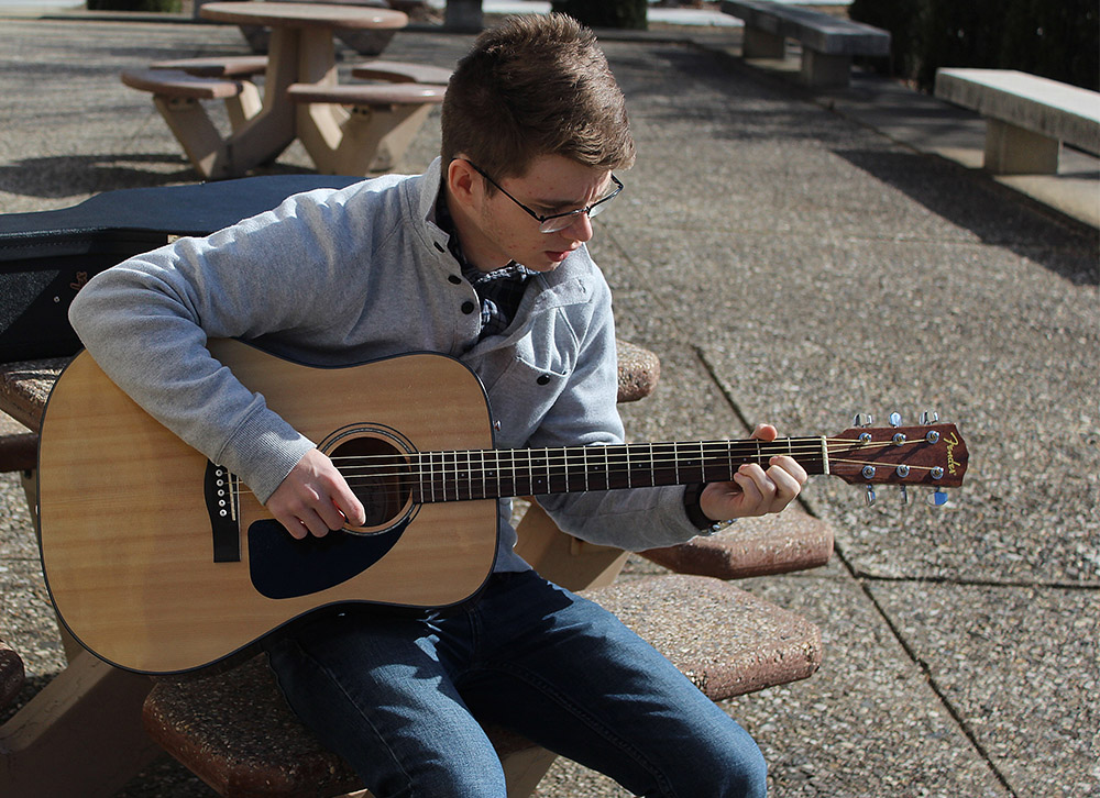 Clayton Lindley, a sophomore communication studies major from Mt. Pulaski, IL, sits outside of Lawson Hall playing his guitar.