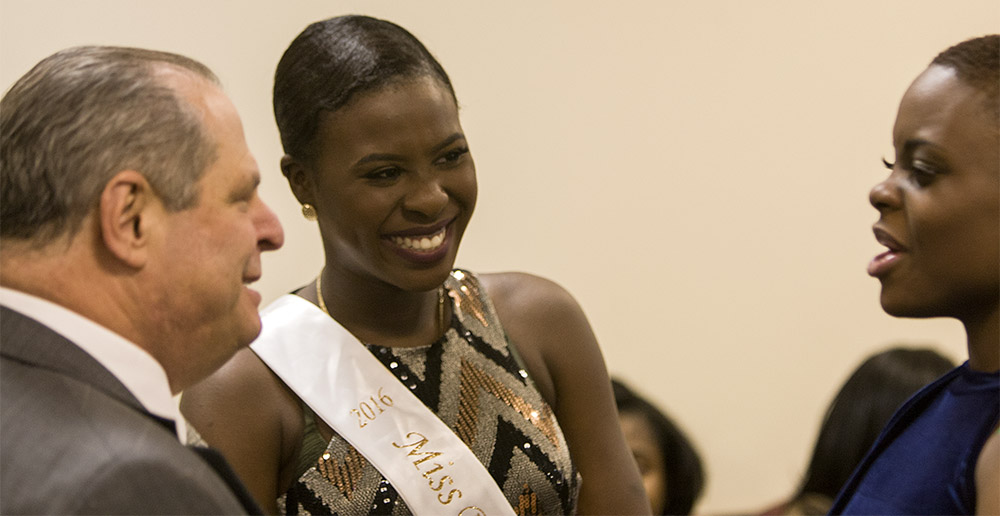 """Julianne Adegoriolu, 2016 Miss Black EIU, center,  chats with President Glassman and contestant Milove Streeter during a meet and greet for the 2017 Miss Black EIU contestants in the Martin Luther King Jr. Union. Adegoriolu, the """"pageant mom,"""" is in charge of prepping and shaping the new contestants to ensure they are prepared for the pageant along with being great leaders on campus."""
