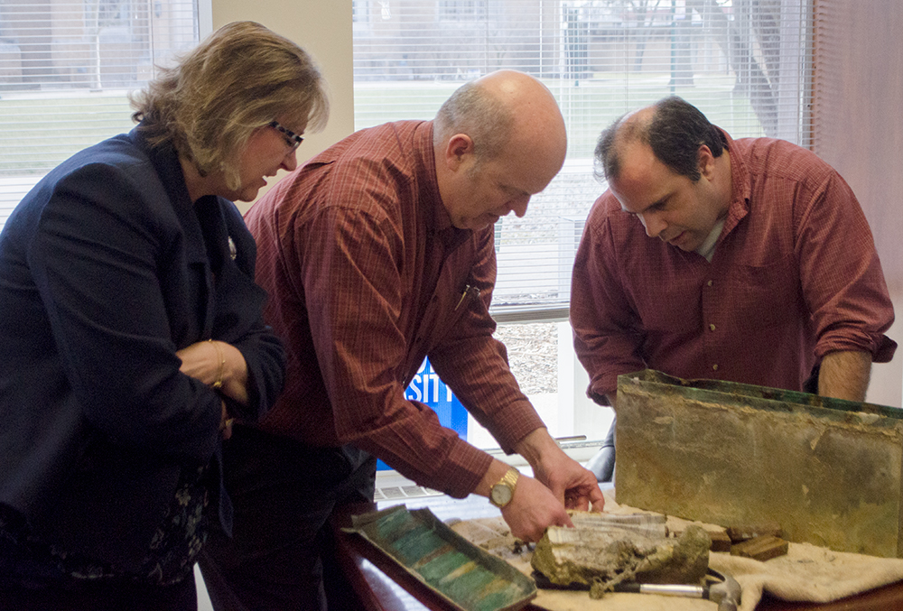 Lynette Drake, interim vice president of student affairs, looks on as Mark Hudson, director of housing and dining, and Bill Schultz, interim university archivist and cataloging librarian, attempt to open materials found inside a time capsule from 1966.
