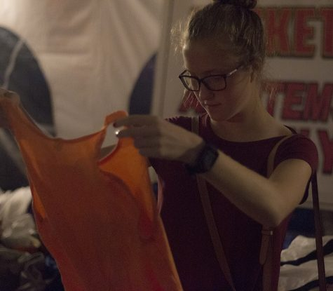Kyla Epplin, a sophomore from Pinkneyville Community High School, inspects a shirt Wednesday night at First to Finish's annual track weekend t-shirt sale in the Gateway Liquors' parking lot. Epplin is competing this weekend and said she is a little nervous but it is not her first time competing.