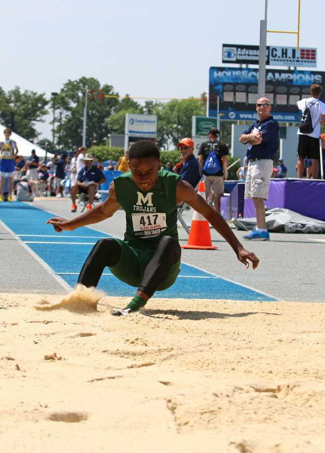 Darrian Crawford, a senior at Madison High School, lands in the sand pit for the triple jump field event during the IHSA Boys State Final Track Meet Saturday at OâBrien Stadium. Crawford placed fourth with a jump of 43 feet, 6 inches.