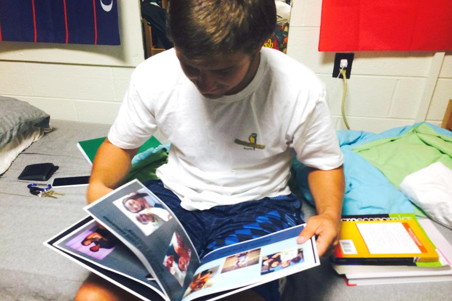 Dominic Recca, a freshman finance major, flips through a scrapbook detailing his time spent with his girlfriend.