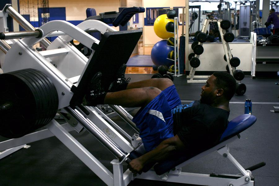 Larry Moore, a senior kinesiology and sports studies major, works out on the leg press machine at the Student Recreation Center Tuesday.