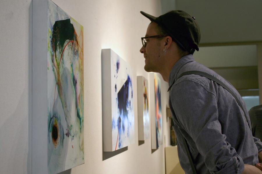 Tom Pekovitch, a graduate art major, studies Chris Kahler, an art professor's painting Dialumens 8A on Thursday at the Tarble Arts Center.