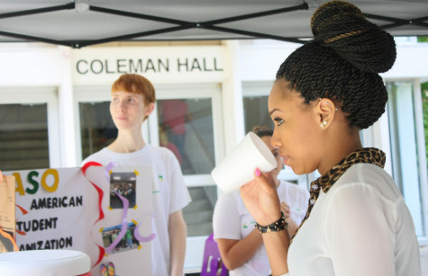 Matthew Wilkie a sophomore foreign languages major serves Debra Wilson a junior accounting major a cup of lemonade promoting the Latin American Student Organization.