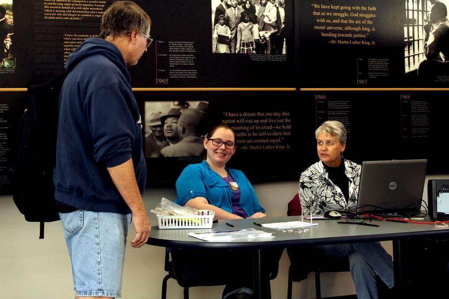 Debi Hilligoss and Danielle Stone, Coles County election judges, discuss politics with Jim Stone, a BSW from the Martin Luther King Jr. University Union, Tuesday in the Bridge Lounge of the Union at the voters table.