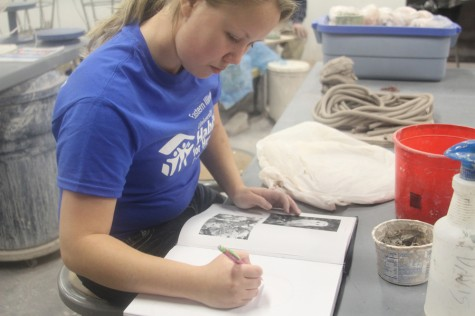 Samantha Kriener, junior 3D arts major, sketches an owl and flowers that will later be a clay coin collector.