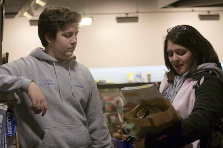 Chynna Miller| The Daily Eastern News Brendan Atwood, a prospective Eastern student, and his mom, Jamee Atwood, buy merchandise Monday during Open House at the Martin Luther King Jr. Union Bookstore. Jamee, a '91 Eastern alumna in the education department, talked about the differences on campus since her time at Eastern. Some of those changes included the Triad Dining Center being made into the Gregg Technology Center and the removal of the McDonald's in the Food Court in the Martin Luther King Jr. Univeristy Union.