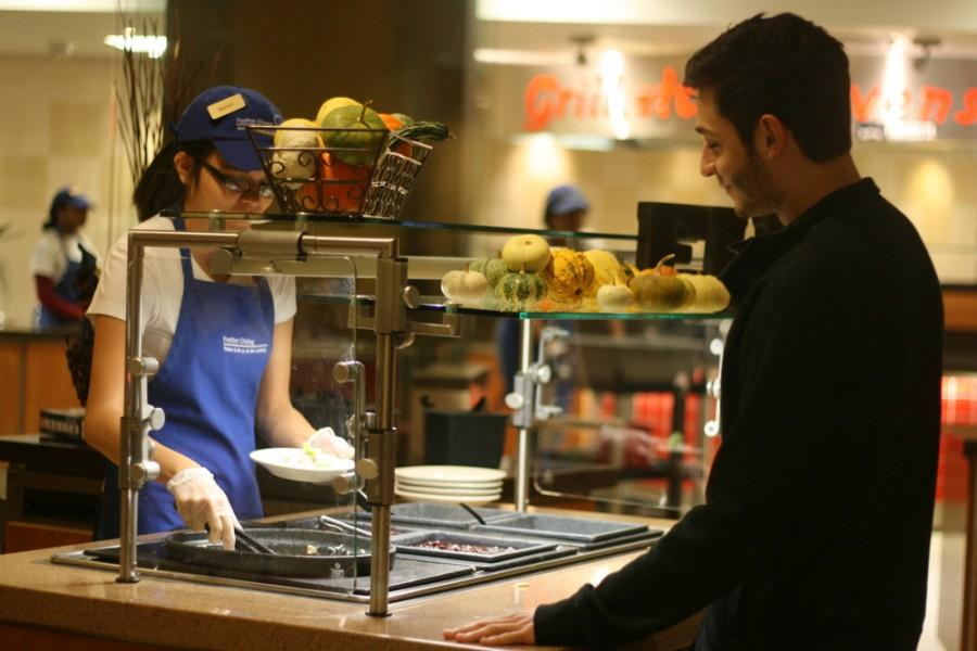Oscar Correa, junior business major, waits for his plate to be filled with Thanksgiving-style food at Stevenson Tower Deli on Wednesday.