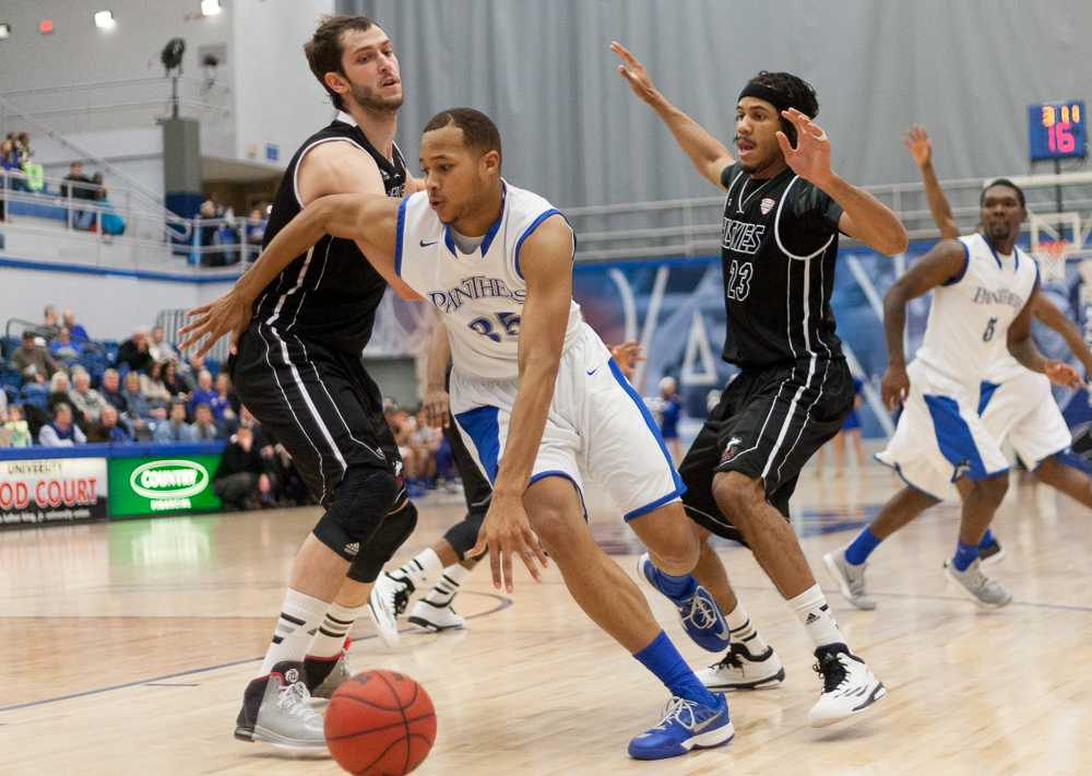 Junior forward Chris Olivier powers through two Northern Illinois opponents during the Panthers' 59-55 win over the Huskies on Dec. 13 at Lantz Arena.  The Panthers beat Indiana State 60-56 on Saturday in Terra Haute, Ind., to improve to 5-6 on the season.  Olivier scored 15 points for the Panthers.