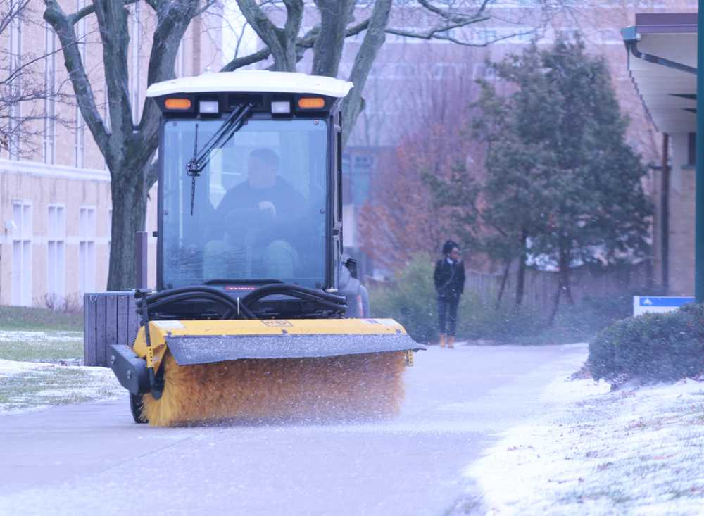 A worker puts down salt to ensures safety for walking students Monday near the Triad.