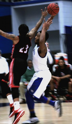 Trae Anderson, a junior forward, attempts to make a lay-up while being defended in the game Saturday in Lantz Arena against SIU Edwardsville. Anderson finished the game with 20 points.