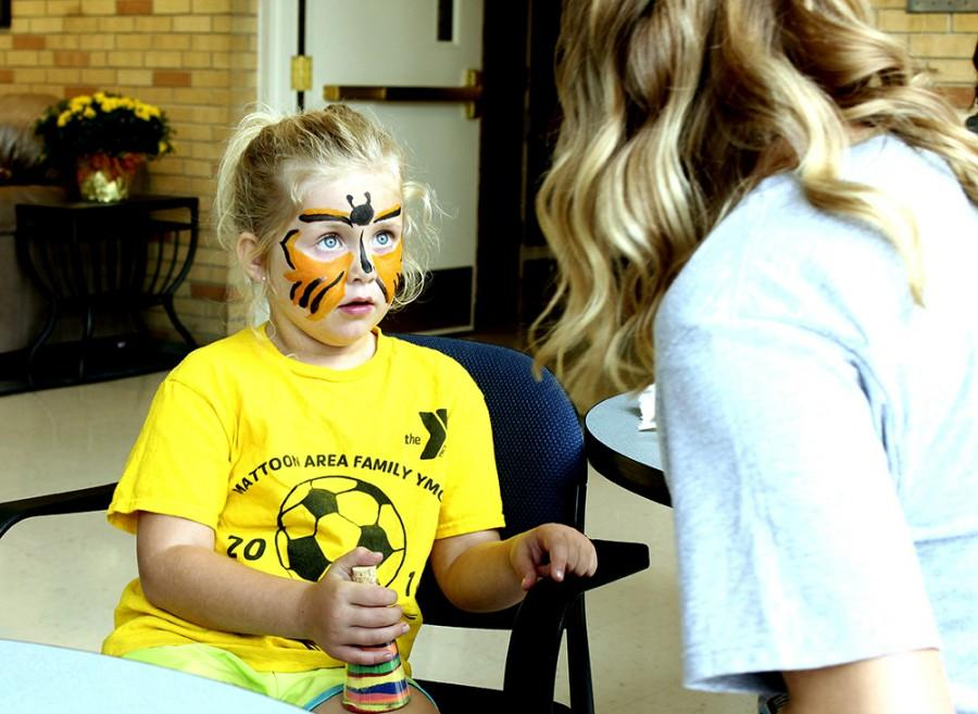 Kelsey Trigg, a Charleston resident, gets her face painted at the Face Painting/Sand Art Bottle event during Family Weekend on Sept. 20, 2014 at the Bridge Lounge in Martin Luther King Jr. University Union.