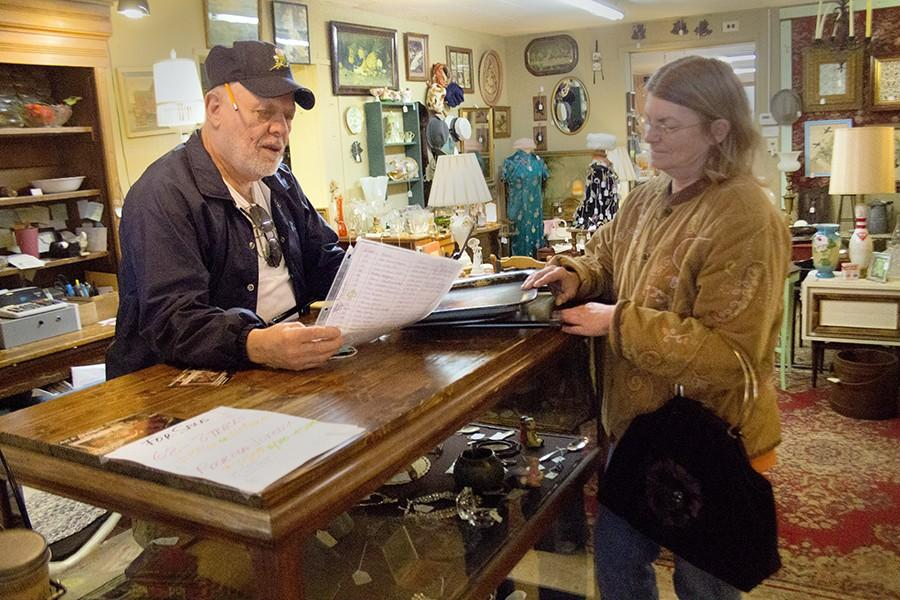 Ron Stearns speaks with a client, Tammy Leonard about an item to potentially sell at Copper Eagle.