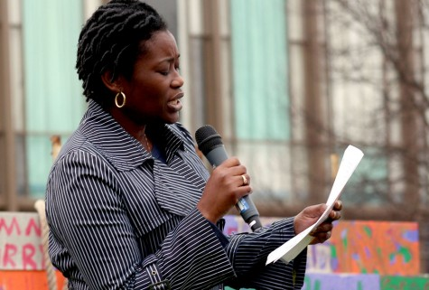 Catherine Polydore, an associate professor in counseling and student developement program, reads a speech at the Wall of Hate tear Friday in the North Quad. Polydore was the first of two speakers to speak at the event.