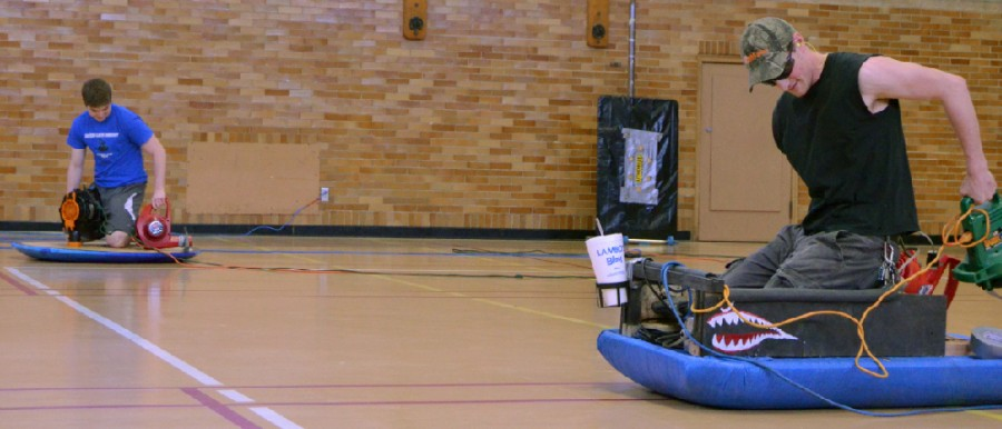 Junior pre-engineering major Tom Sticha and sophomore pre-engineering major Paul Blackmore race their race their hovercrafts on Saturday in the McAfee Gym.