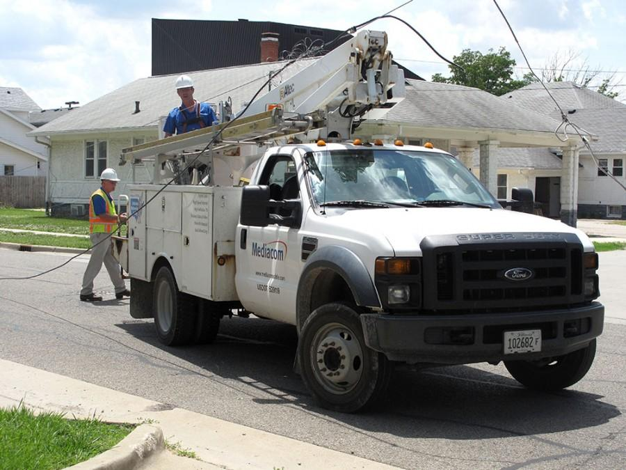 Mediacom workers fix a fallen cable wire on Ninth Street Thursday after a semitrailer driving past pulled it down.