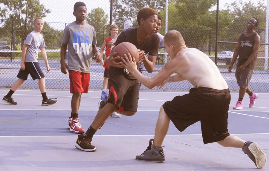 Two players fight for possession after a long rebound during a pick-up basketball game Monday outside Lantz Arena.