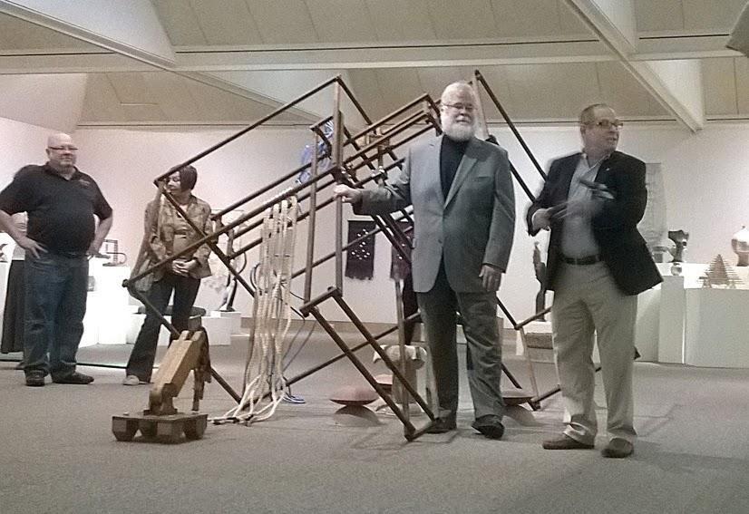 Jeff Boshart (left) and President David Glassman (right) speak to patrons at the art show, talking in part about the piece in the middle of the show, which incorporates styles from each of the emeritus professors.