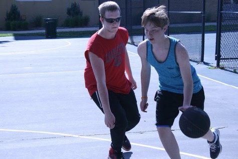 Todd Elliot, 16, Charleston, dribbles past his defender duiring a pick-up basketball game   Tuesday afternoon on the basketball courts outside of Lantz Arena.