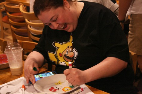 "Kaci Strohl, of Charleston, designs a bowl with a ""Super Mario"" theme Monday during the ""Bowls of Fun"" event at Jackson Avenue Coffee sponsored by HOPE of East Central Illinois to raise awareness of domestic violence."