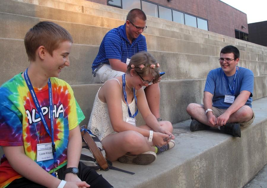 From left to right: Lizzie Krouse, of Edwards County High School, and friends Stephanie Hill, Andrew Weger and Paul Williams, all of Red Hills High School, catch up with one another on the Doudna steps Sunday afternoon after participating in introductory Eastern Music Camp sessions. Hill, a recently graduated senior who plans to attend Vincennes University in Indiana, said she has attended the band camp at Eastern for the past six years and has met many friends and learned a lot about music in the process.