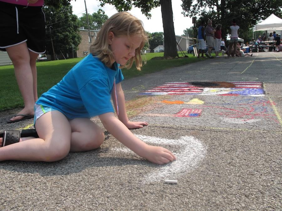A child draws the White House for the Chalk-In competition of Red, White and Blue Days Saturday in Morton Park.
