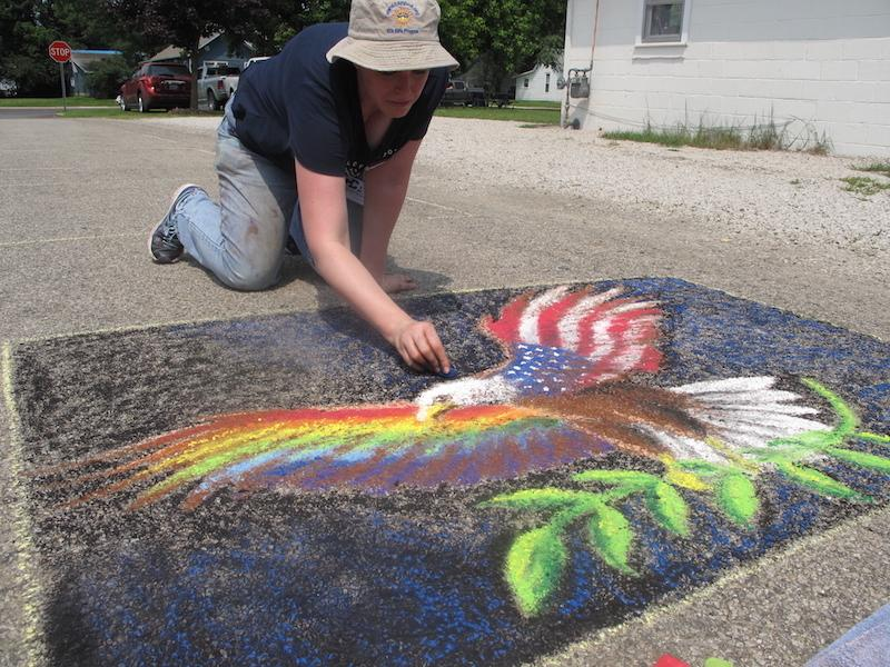 Vice president of the arts council completes an entry for the Chalk-in Saturday as part of Red, White and Blue Days in Morton Park