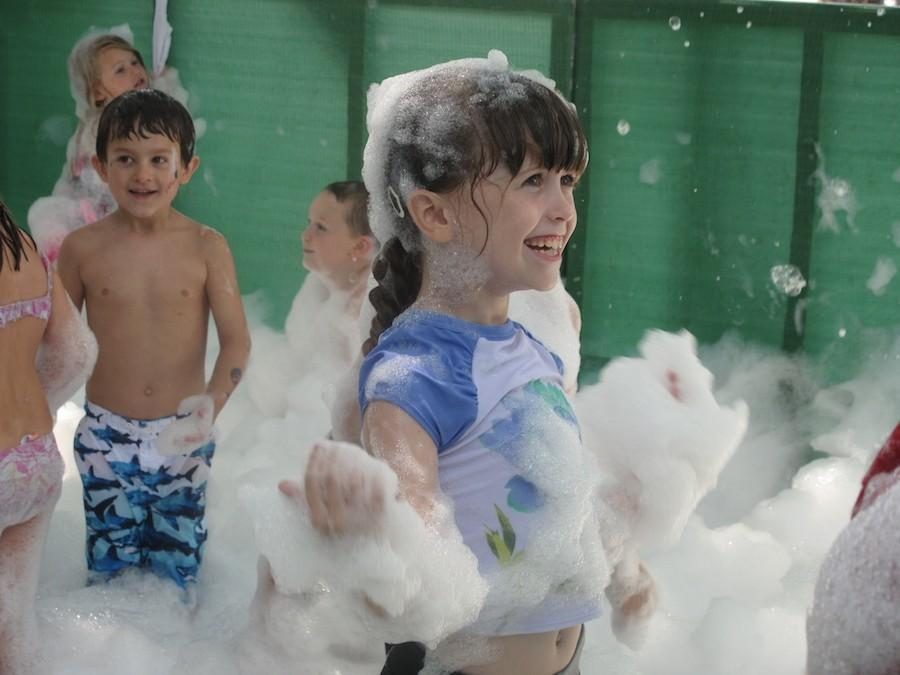 Children play in the bubble area before hosing off at a fire hose Saturday in Morton Park