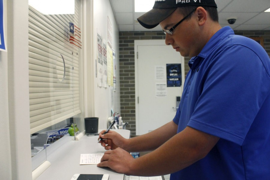 Philip Blank, a junior kinesiology and sports studies major, fills out a form to purchase his parking permit Wednesday in the Eastern Illinois University Police Department.