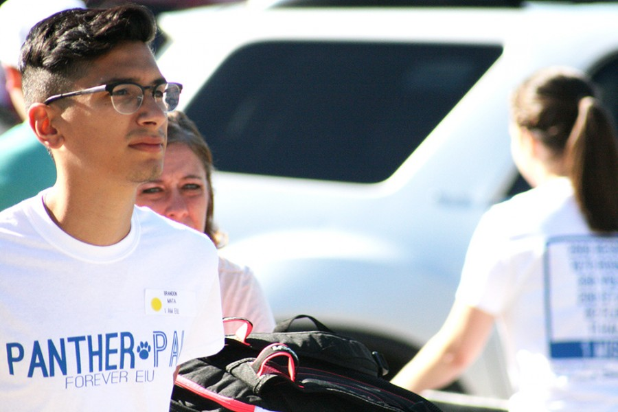 Brandon Mata, a senior special education major helps parents push carts outside of Stevenson Hall, Thursday morning during Move-In Day.
