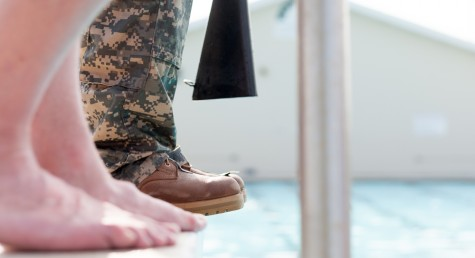 An Eastern ROTC cadet hesitates to jump into the water during combat water training on Thursday at the Charleston Rotary Pool.