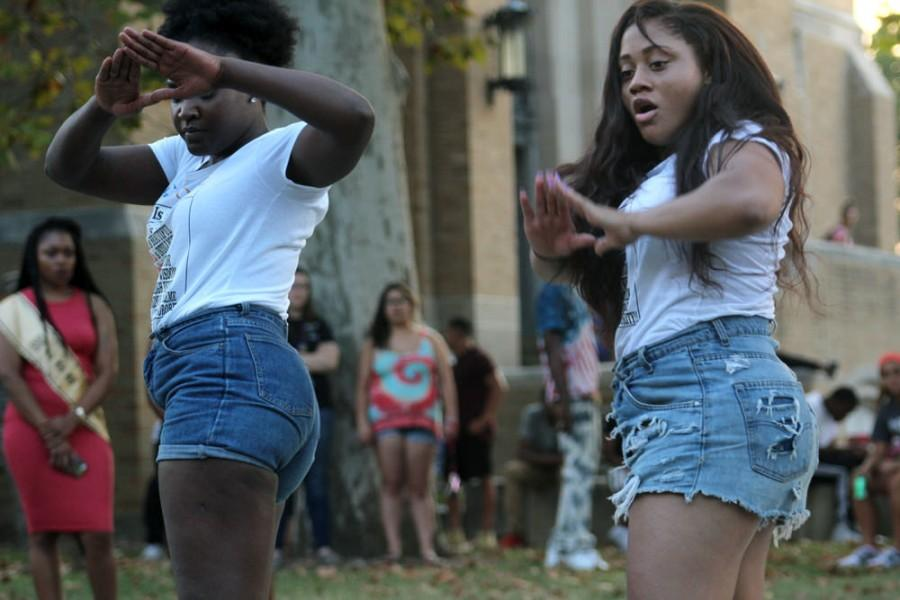 Ashley Howard, a senior communication studies major, and Kathryn McIntosh a senior kinesiology and sports studies major, holds up the Delta Sigma Theta hand sign during their performance with their sorority at the Meet the Greeks yardshow Thursday near the steps of the Dounda Fine Arts Center.
