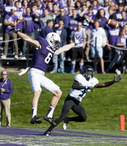 Northwestern's Mike McHugh and red-shirt senior defensive back Antoine Johnson leap for the ball during Eastern's 41-0 loss to Northwestern on Saturday at Ryan Field in Evanston, Ill.