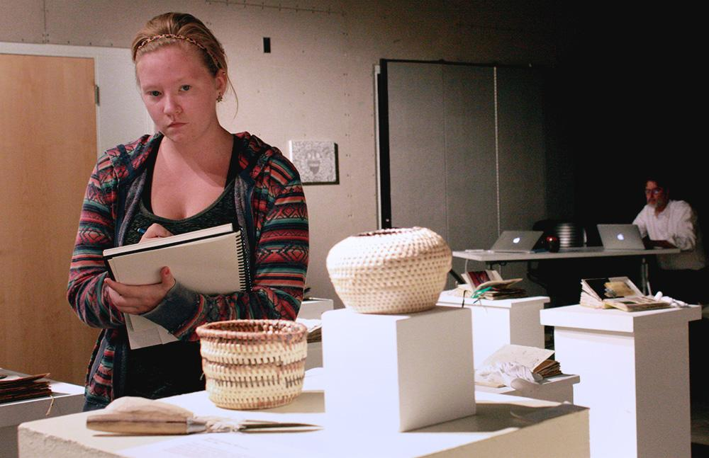 Maeve Burke, a sophomore communication disorders and sciences major, observes the Indonesian basket display on Wednesday in the 1910 Art Gallery at Doudona. This display is part of a gallery based on the Indonesia Study Abroad Activites that occured this past summer.