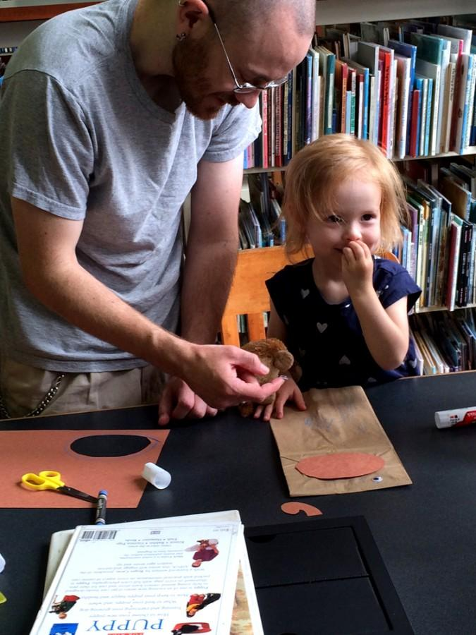 David Cook II and his daughter, Opal, 2 make a monkey puppet during Curiosity Day, on Saturday in Booth Library. Curiosity Day recognized the 70th anniversary of Curious George.