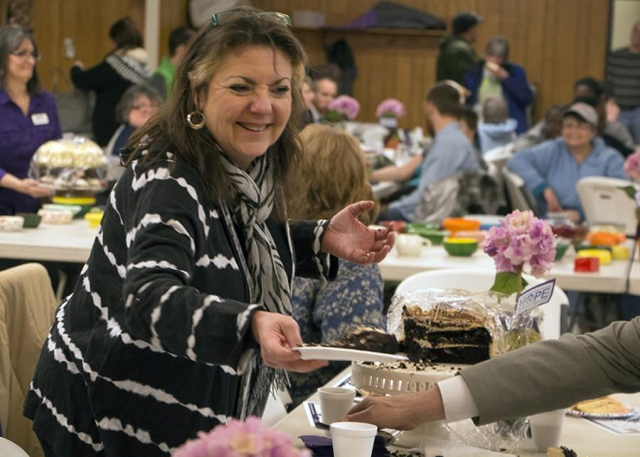 Mary Bower passes out double chocolate cake with caramel cream to friends at the Bowls for HOPE fundraiser at the St. Charles Borromeo Church on Feb. 16.