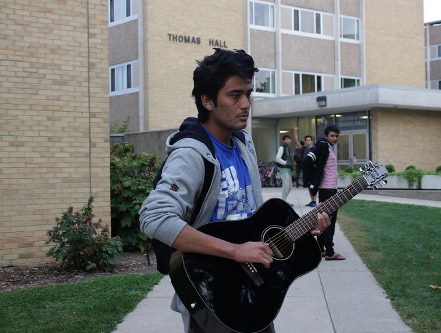 Kamal Simkhada, a freshman accounting major, strums a guitar outside of Thomas Hall on Monday. Kamal has been playing guitar for five years.