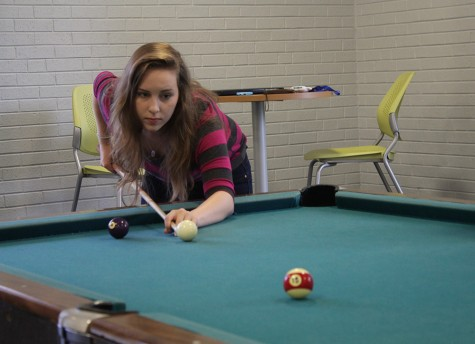 Kelsey Higgins, a freshman accounting major shoots pool on Monday in the lobby of Thomas Hall. Higgins said she shoots pool everyday with her friends.