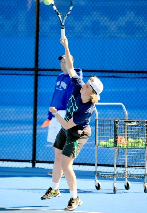 Grace Summers, a freshmen, practices a serve at the Darlings Courts Tues. March 31, 2015
