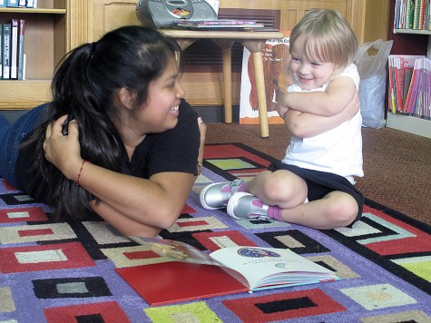 Gladys Valentin, a senior elementary education major and the President of LASO, reads a book with Aubrey Malak, a three year old Charleston resident, during Latino Hertiage Story Time on Sept. 26 in Booth Library.