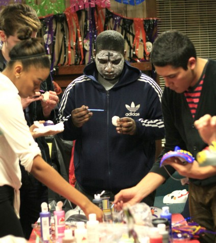 Darell Brewster, a sophmore communactions studies, paints a mask for the Day of the Dead party at the Cultural Center on Oct. 30, 2014.