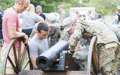 Members of Eastern's ROTC scramble to fix the cannon as new members of the Cannon Crew become acquainted with the process on Thursday between Klehm Hall and the Human Services Building.