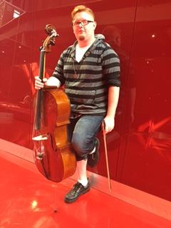 Logan Wood, freshman music performance and psychology major, stands with cello in the red zone lounge.