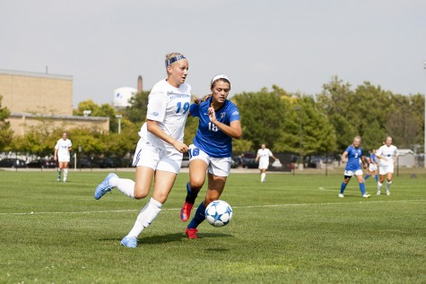 Freshman Kate Olson runs alongside IPFW's Paityn Fleming during the Panthers' 3-1 victory on Sept. 4 at Lakeside Field.