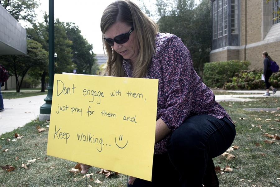 Paige Roberts, the campus minister at the Wesley Foundation, posts up the Grace Space signs in protest to Mikhail Savenko and Ryan Simpkins speaks with students on Monday in the Library Quad. Roberts said the Grace Space allowed them to silently counter protest against radical evangelists.