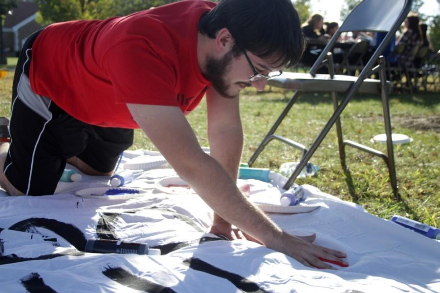 """Henry Schmidt, a senior biological sciences major, puts his handprint on the """"These Hands Don't Haze"""" Banner during the Unity Banner Anti Hazing Event on Thursday in Greek Court."""