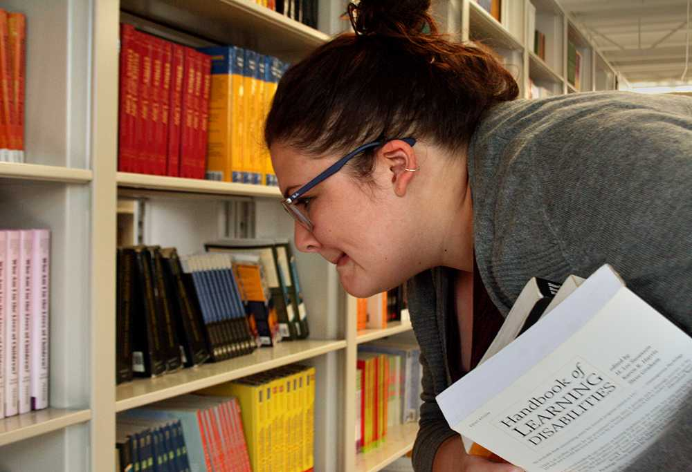 Hillary Young, a graduate of communication disorders and sciences, chooses books to purchase at Textbook Rental Services on Monday.