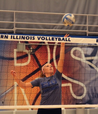 Sophomore middle hitter Allie Hueston tips the ball over the net during practice Tuesday in Lantz Arena.