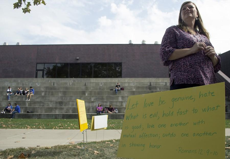 Paige Roberts, the campus minister at the Wesley Foundation, watches on as  Mikhail Savenko and Ryan Simpkins speak with students on Monday in the Library Quad. Roberts said the Grace Space allowed them to silently counter protest against radical evangelists.